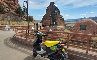 scooter in front of red rocks miner statue